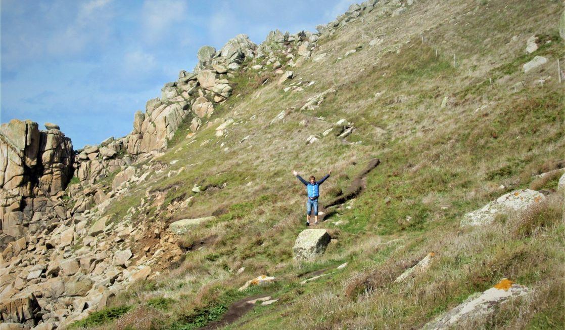 Walker waving on the coast path